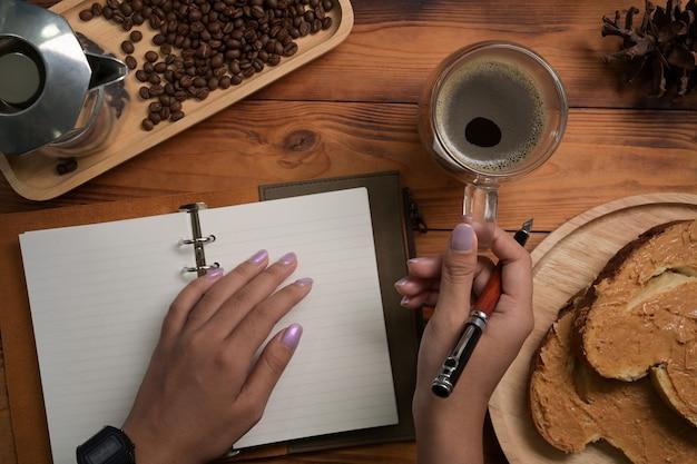 Vrouw met glas koffie en het maken van aantekeningen op notebook.