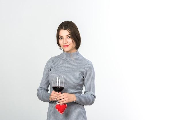Vrouw met glas wijn en een klein hart in handen