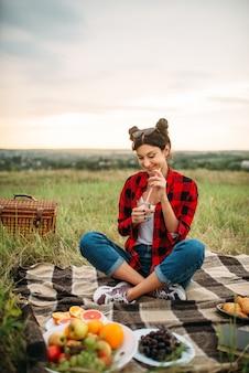 Vrouw met glas wijn, picknick op weide