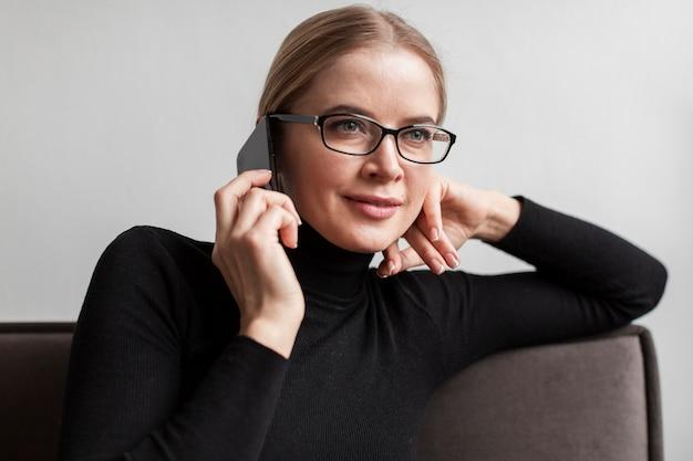 Vrouw met glazen die bij telefoon spreken