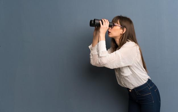 Vrouw met glazen over blauwe muur en kijkend in de afstand met verrekijker