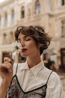 Vrouw met golvend haar in licht overhemd met zwarte kant die bloem snuift in stad. inschrijving vrouw met rode lippen en kort haar vormt op straat.