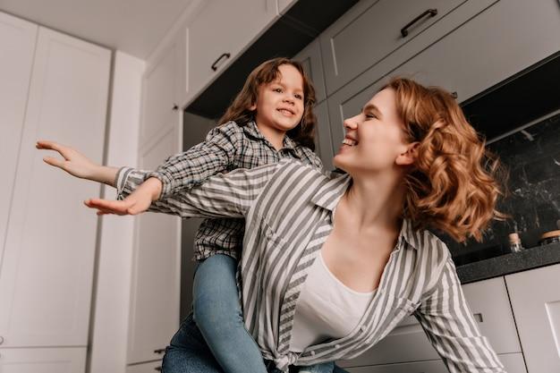 Vrouw met golvend haar speelt met haar dochter en poseert als vliegtuigen.