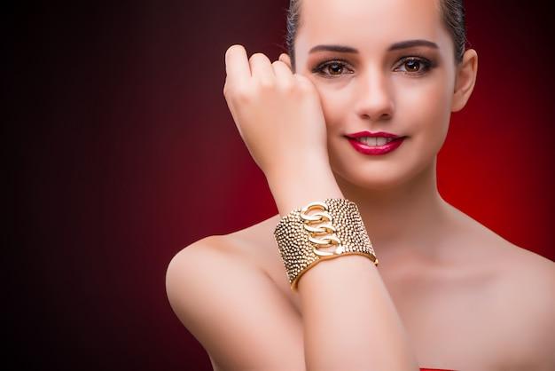 Vrouw met gouden armband in schoonheidsconcept