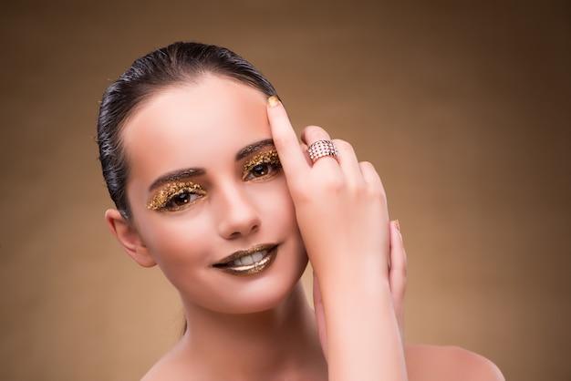 Vrouw met gouden ring in schoonheidsconcept