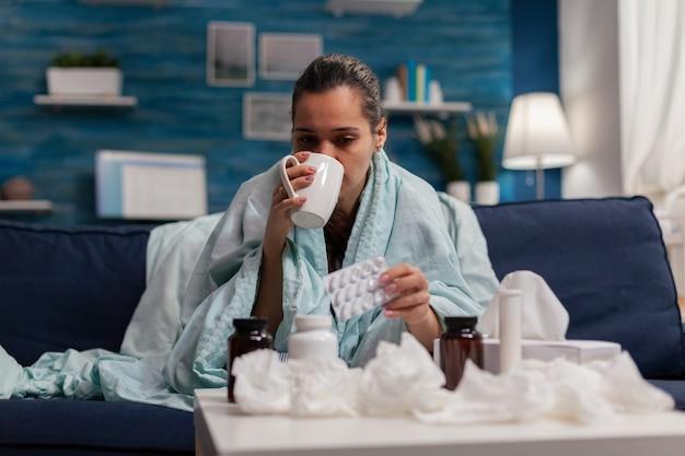 Vrouw met griep die medicijnen drinkt op de bank thuis