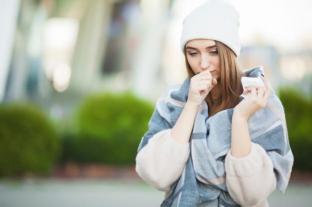 Vrouw met griep in openlucht gekleed in glb