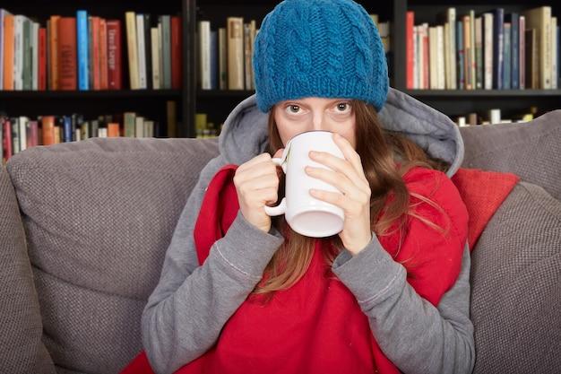 Vrouw met griep zittend op de bank