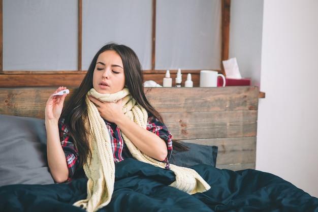 Vrouw met griepvirus dat in bed ligt, meet zij haar temperatuur met een thermometer en raakt haar voorhoofd.