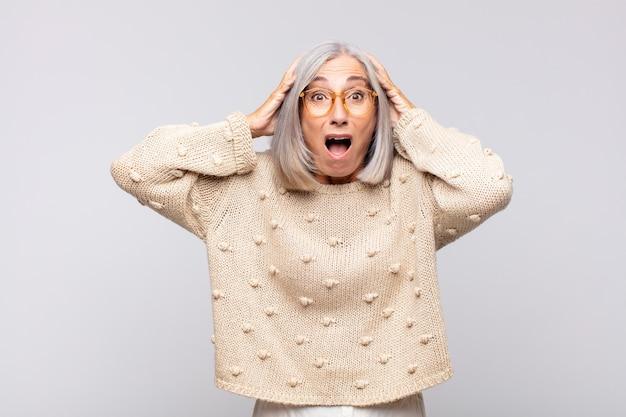 Vrouw met grijs haar die opgewonden en verrast kijkt, met open mond en beide handen op het hoofd, zich een gelukkige winnaar voelt