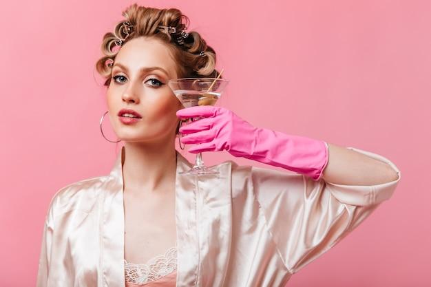 Vrouw met grijze ogen in roze gewaad met martiniglas op geïsoleerde muur
