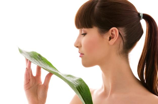 Vrouw met groen blad over wit