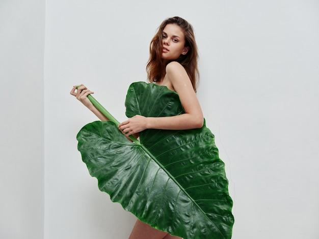 Vrouw met groen palmblad glamour naakt lichaam