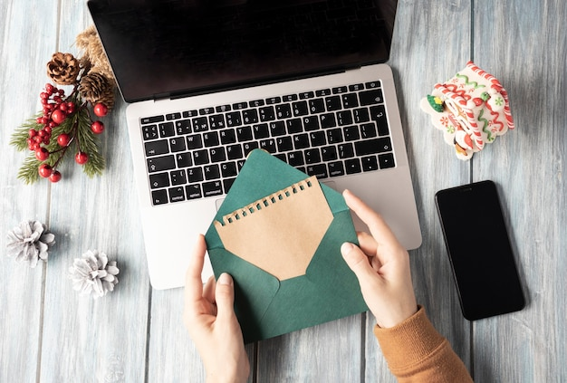 Vrouw met groene envelop over laptop, kerstsfeer op kantoor