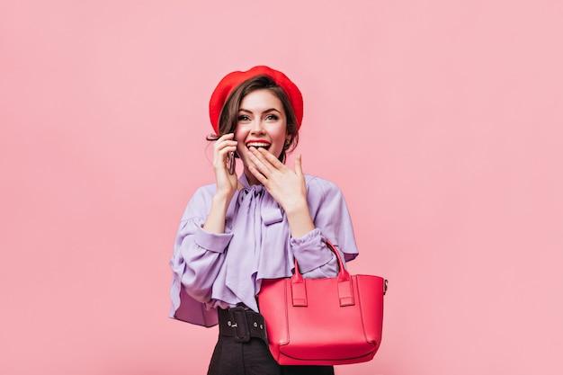 Vrouw met groene ogen bedekt haar mond en praat over de telefoon. dame in rode baret houdt tas op roze achtergrond.