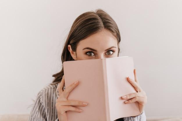 Vrouw met groene ogen in gestreepte pyjama kijkt naar voren en bedekt haar gezicht met notitieboekje