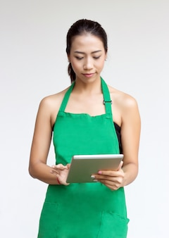 Vrouw met groene schort tablet gebruiken voor sociale media
