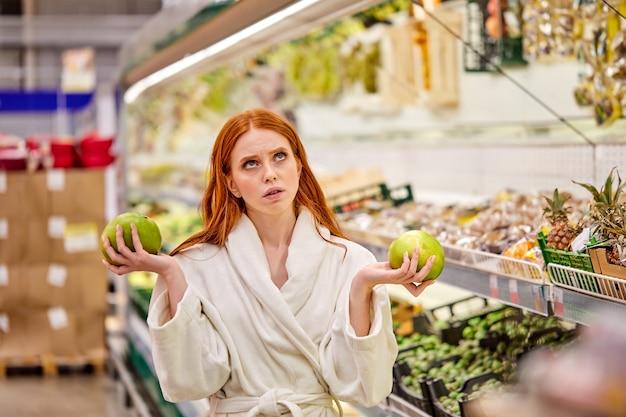 Vrouw met groene vruchten in handen denken welke te kopen, vergelijken, badjas dragen
