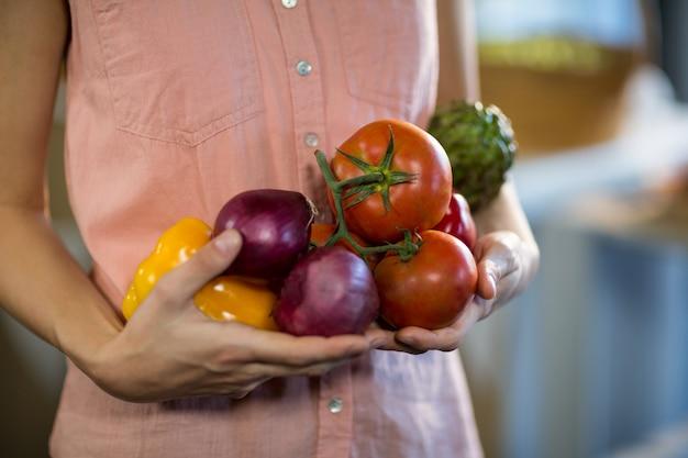Vrouw met groenten bij supermarkt