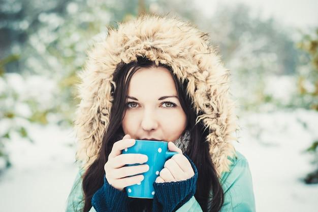 Vrouw met grote blauwe mok hete drank tijdens koude dag.