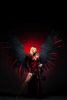 Vrouw met grote engelenvleugels op zwarte muur.