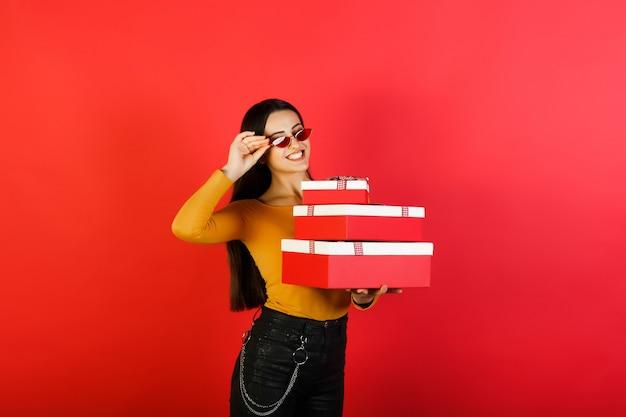 Vrouw met grote geschenkdozen op de rode achtergrond.