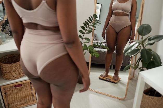 Vrouw met grote maten in ondergoed controleert haar gewicht op de weegschaal