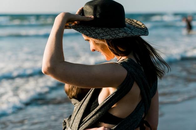 Vrouw met haar baby op het strand in de zomervakantie bij zonsondergang