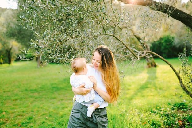 Vrouw met haar babymeisje in haar armen onder een olijfboom op een zonnige dag
