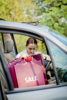 Vrouw met haar boodschappentassen in de auto - winkelen concept.