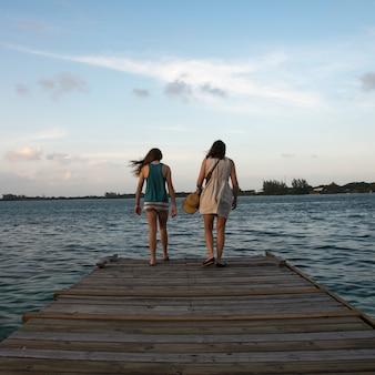 Vrouw met haar dochter die zich op een pijler bevinden en op zee, utila eiland, baaieilanden, honduras kijken