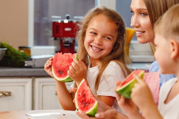 Vrouw met haar dochter en zoon die watermeloen eten in de keuken
