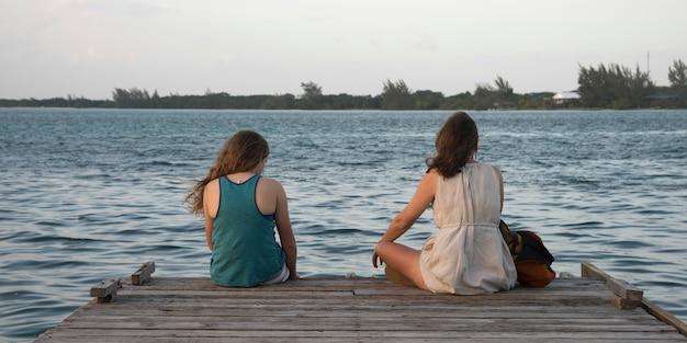 Vrouw met haar dochter zittend op een pier, utila island, baai-eilanden, honduras