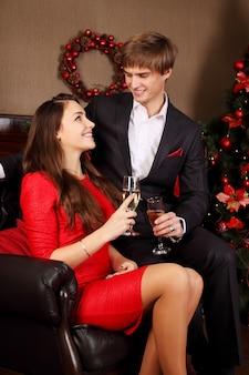 Vrouw met haar echtgenoot die bij de kerstboom zit