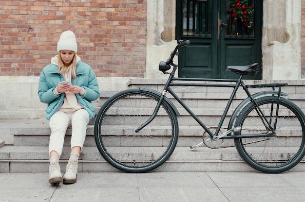 Vrouw met haar fiets die een pauze neemt