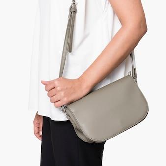 Vrouw met haar grijze leren schoudertas