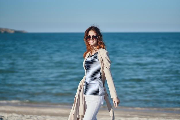 Vrouw met haar handen boven haar hoofd gebaren op het strand in de buurt van de zomerhemel van de zee