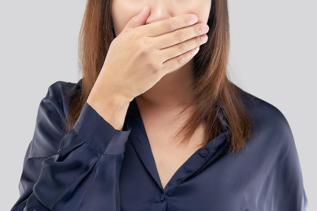 Vrouw met haar handen op haar mond vanwege een slechte adem of halitose