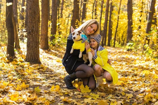 Vrouw met haar hond in de herfstpark. meisje speelt met jack russell terriër buitenshuis. huisdier en mensen