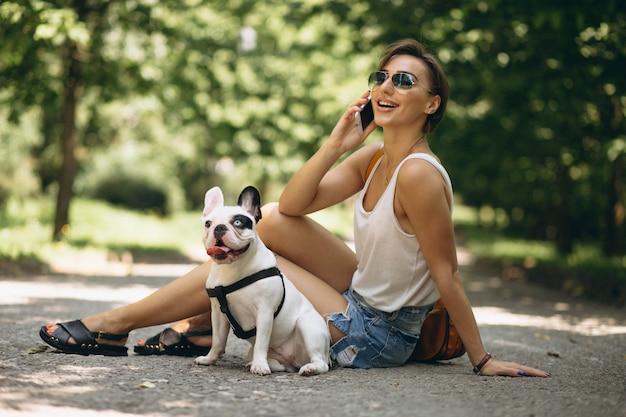 Vrouw met haar huisdieren franse buldog die op de telefoon spreekt