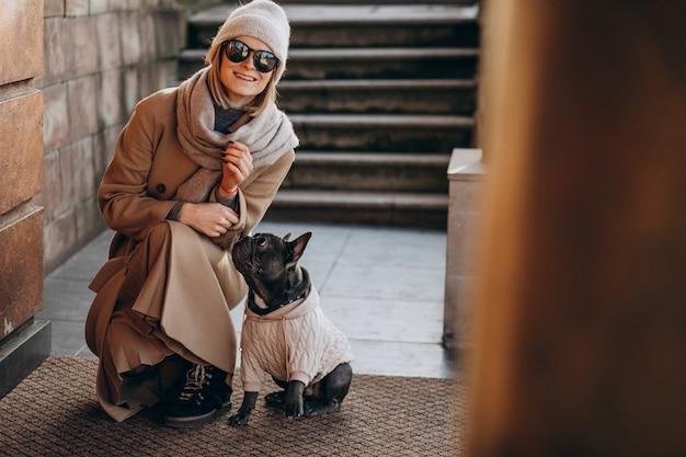 Vrouw met haar huisdieren franse buldog die weggaat