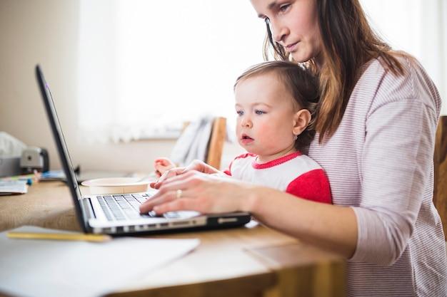 Vrouw met haar kind dat aan laptop over houten bureau werkt