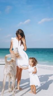 Vrouw met haar kleine dochter die met honden bij het strand door de oceaan speelt