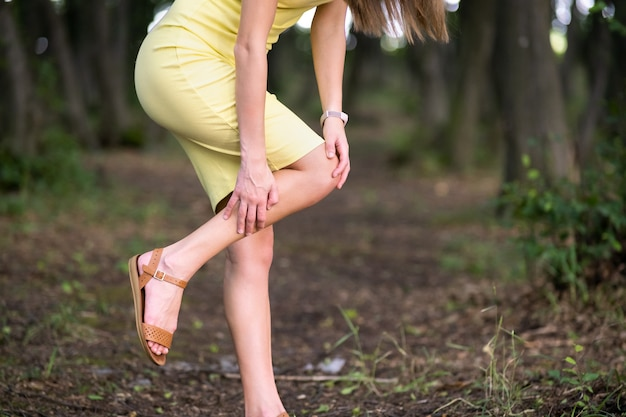 Vrouw met haar knie met handen met gewrichtspijn.
