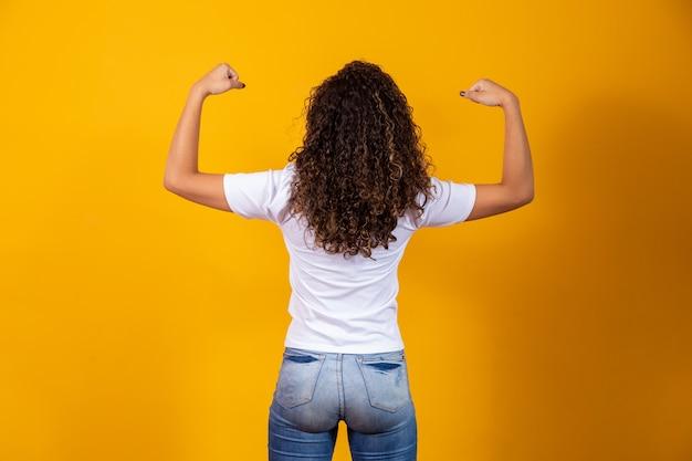 Vrouw met haar rug die haar armspieren laat zien. sterk concept