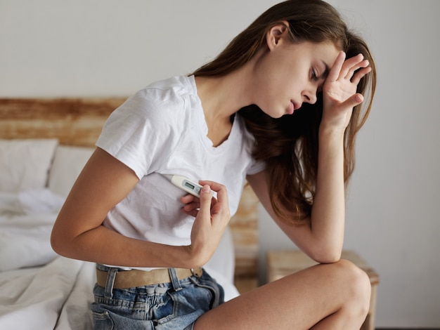 Vrouw met haar voorhoofd met haar handthermometer okseltemperatuur. hoge kwaliteit foto