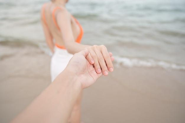 Vrouw met haar vriendje hand loopt samen op het strand.