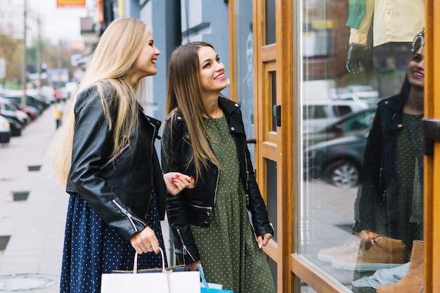 Vrouw met haar vrouwelijke vriend die venster het winkelen doet