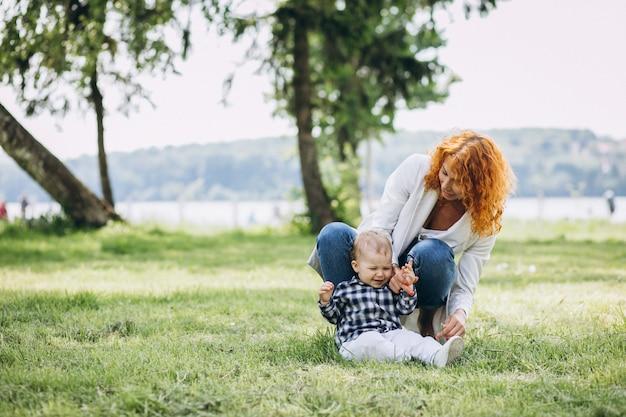 Vrouw met haar zoon die pret in park heeft