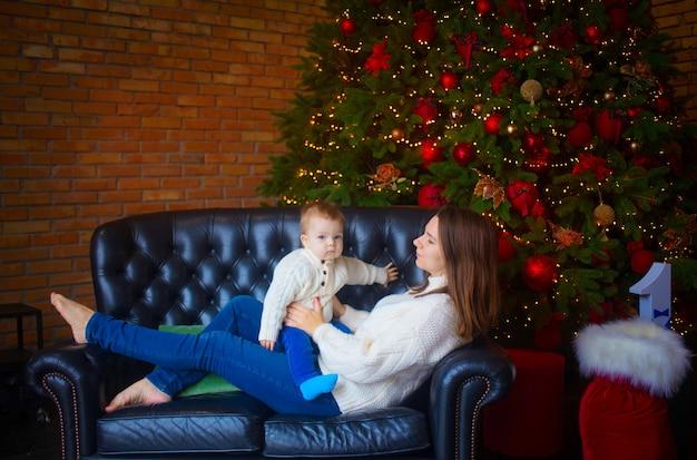 Vrouw met haar zoontje in de buurt van een kerstboom in een donker interieur.